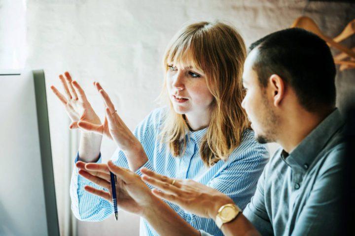 Mulher explicando algo em frente a um computador para um homem