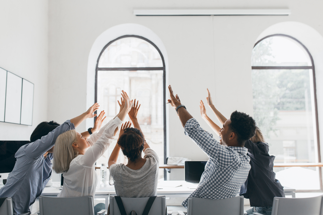 Grupos de pessoas, sentadas em volta de uma mesa de escritório, comemorando com as mãos para cima.