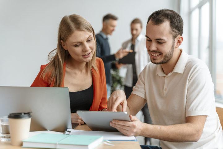 Homem e mulher fazem a consultoria tributária de seu negócio